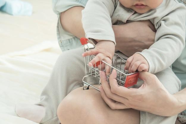 Carrinho de compras pequeno e turva bebê e mãe