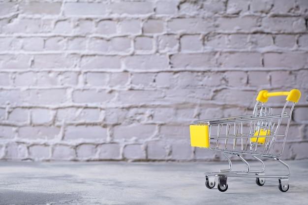 Carrinho de compras pequeno em fundo cinza. espaço de texto