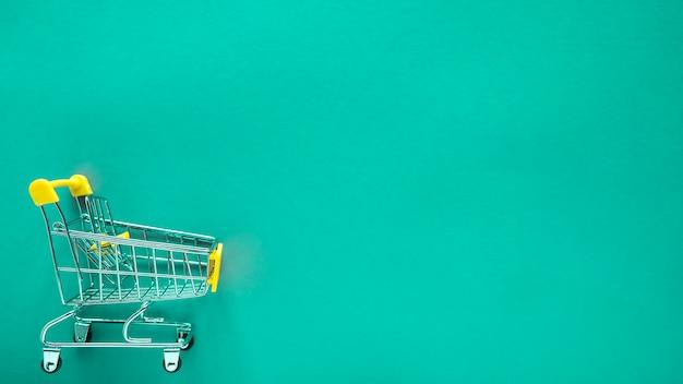 Carrinho de compras pequeno em verde com espaço de cópia