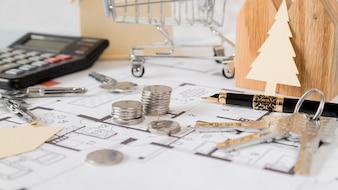 Carrinho de compras; pilha de moedas; chaves; papel cortado em árvore de Natal e caneta-tinteiro no plano de construção