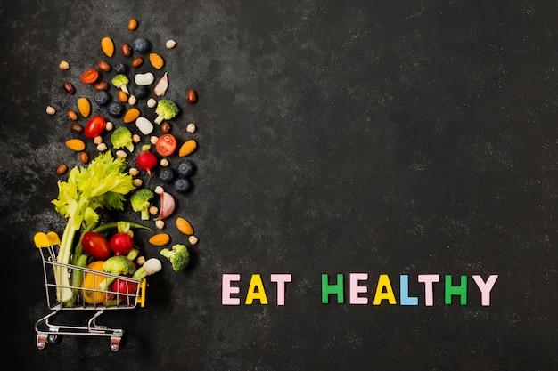 Carrinho de compras plana leigos com alimentos saudáveis