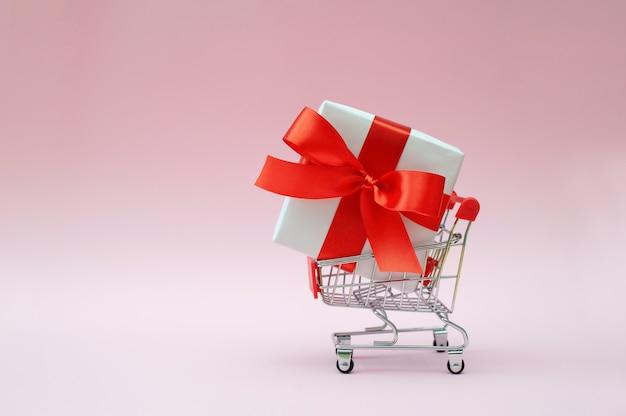 Carrinho de compras vazio com caixa de presente e produto de laço vermelho em fundo rosa. conceito de venda ou compra.