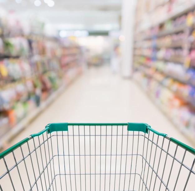 Carrinho de compras vazio com desfoque abstrato de supermercado loja corredor e prateleiras de produtos com fundo desfocado.