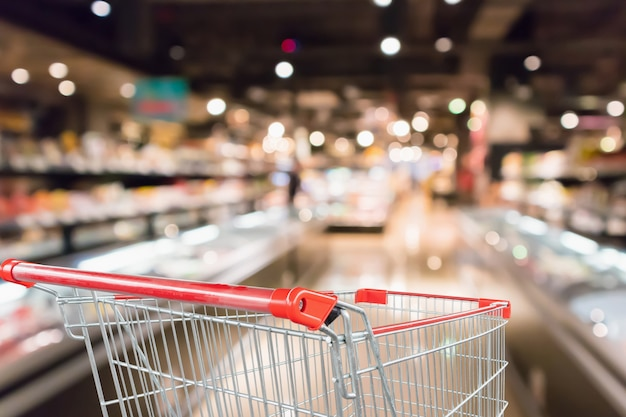 Carrinho de compras vazio com desfoque abstrato de supermercado loja de descontos e interior de prateleiras de produtos desfocado