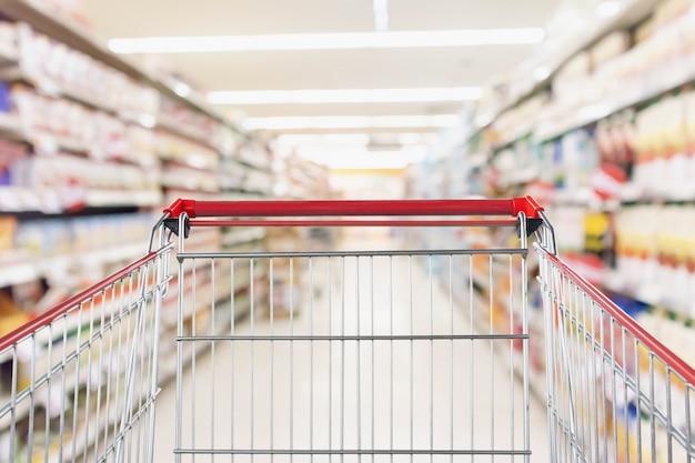 Carrinho de compras vazio com desfoque abstrato de supermercado loja de descontos e interior de prateleiras de produtos