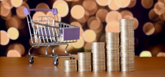 Carrinho de compras vazio e pilhas de dinheiro no gráfico de crescimento no fundo de luzes de natal coloridas bokeh