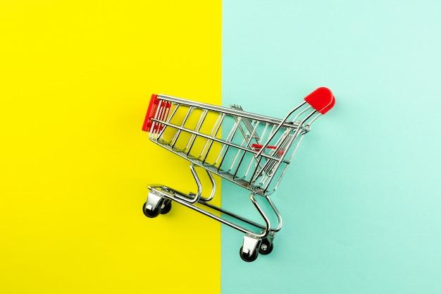 Carrinho de compras vazio em fundo amarelo e azul