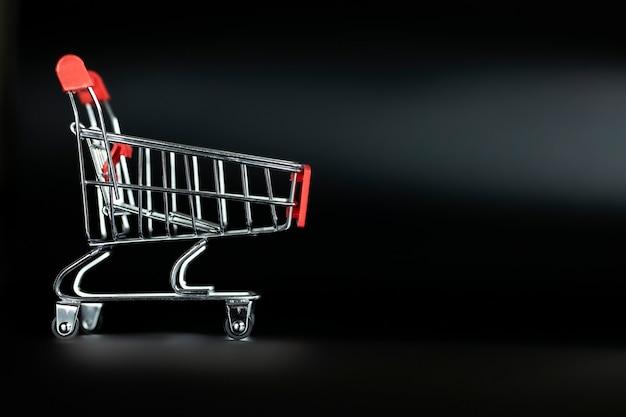 Carrinho de compras vazio em fundo preto com espaço de cópia comercial e conceito de sexta-feira negra