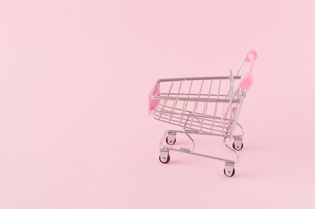 Carrinho de compras vazio em um fundo rosa com um grande espaço de cópia conceito de compra online