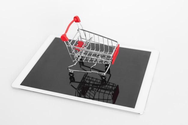 Carrinho de compras vazio na tabuleta digital, isolado no branco