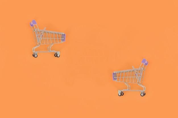 Carrinho de compras vazio pequeno encontra-se em um papel colorido pastel