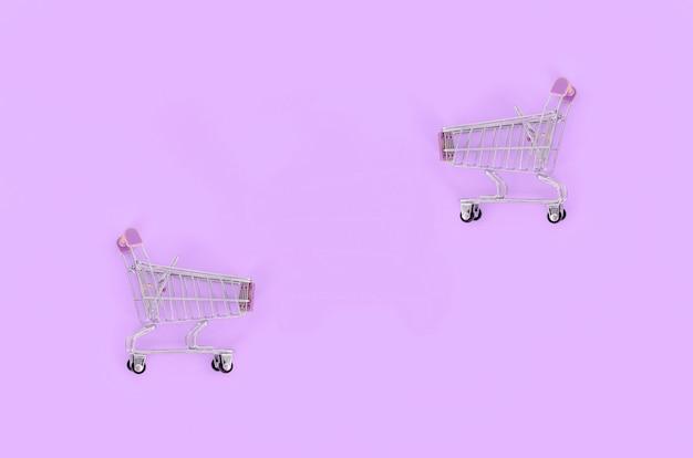 Carrinho de compras vazio pequeno encontra-se em um violeta pastel