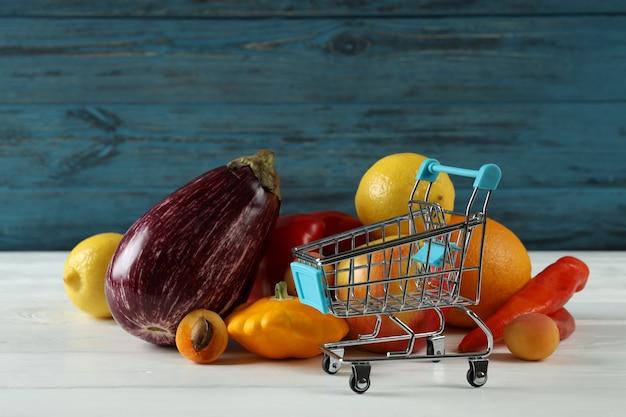 Carrinho de compras, vegetais e frutas na mesa de madeira