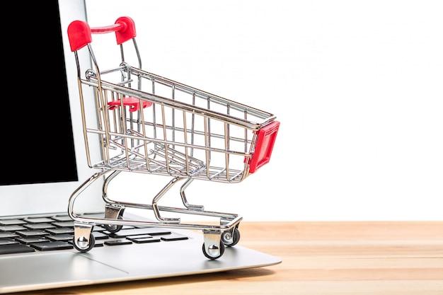 Carrinho de compras vermelho em um laptop isolado.