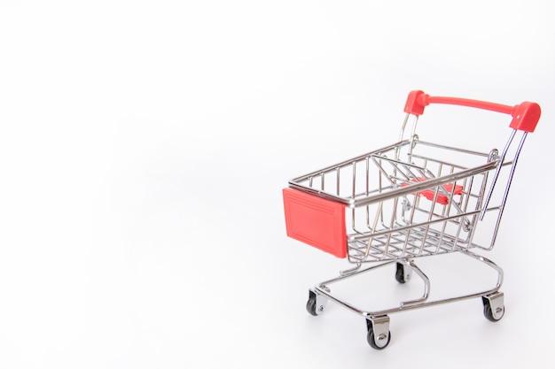 Carrinho de compras vermelho ou carrinho de supermercado vazio isolado no fundo branco, com espaço de cópia