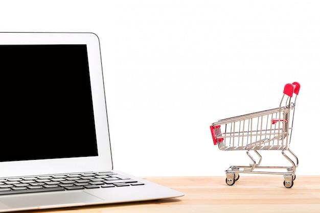 Carrinho de compras vermelho perto de laptop isolado no fundo branco