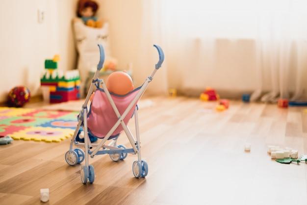 Carrinho de criança com boneca na sala de jogos. copie o espaço para texto. jogo criativo para crianças. creche