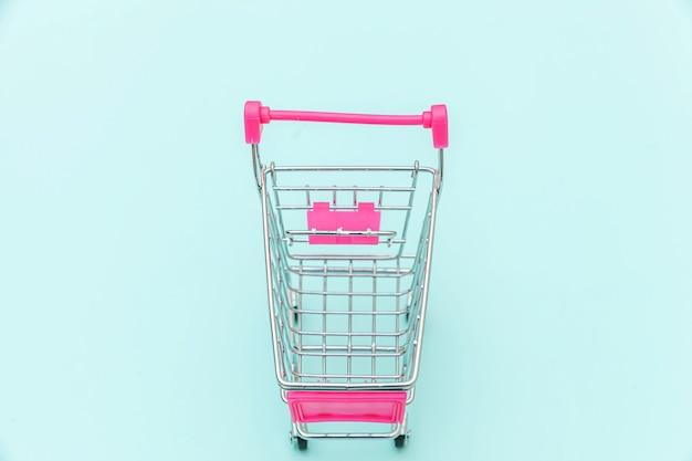 Carrinho de empurrar de mercearia de pequeno supermercado para compras isolado no espaço de cópia de fundo azul