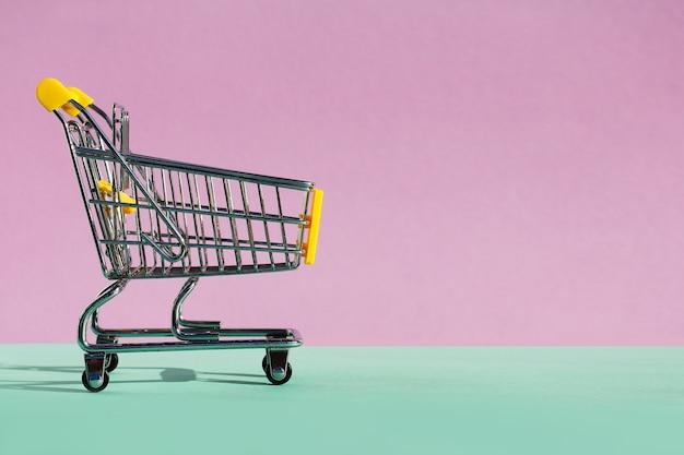Carrinho de empurrar de supermercado pequeno para comprar brinquedos com rodas em fundo verde-violeta. o conceito de consumo, compras na loja, vendas. copie o espaço