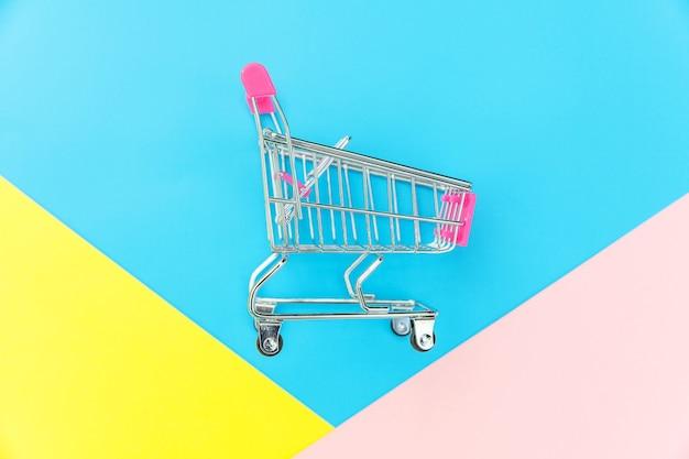 Carrinho de empurrar de supermercado pequeno para comprar brinquedos com rodas isoladas na mesa geométrica na moda colorida pastel rosa amarelo azul copie o espaço. conceito de consumidor de loja de mercado de compra de venda.