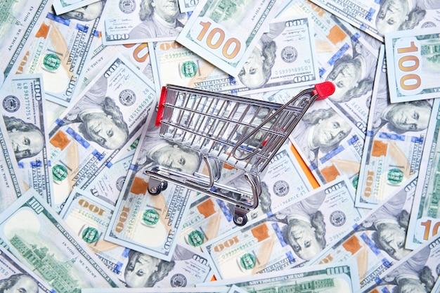 Carrinho de ferro pequeno de supermercado em fundo de dinheiro