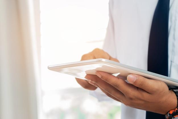 Carrinho de homem de negócios usando o dispositivo de computador portátil