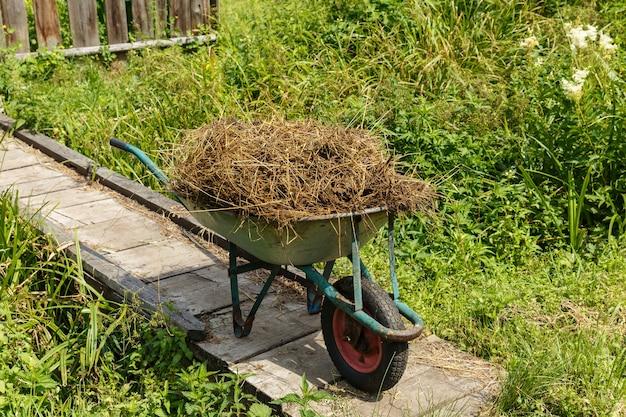 Carrinho de jardim com esterco de vaca natural. o carrinho fica em uma ponte de madeira.
