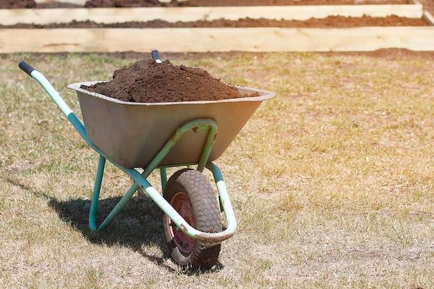 Carrinho de jardim com húmus e pá