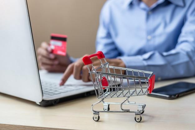 Carrinho de mini, empresário asiático, segurando o cartão de crédito e usando o laptop