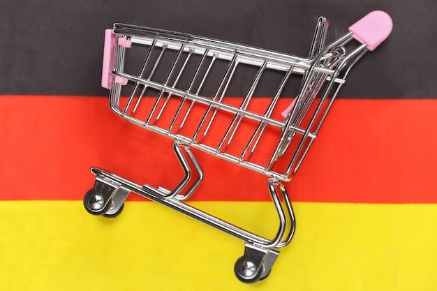 Carrinho de mini supermercado no fundo desfocado da bandeira da alemanha. conceito de compras.