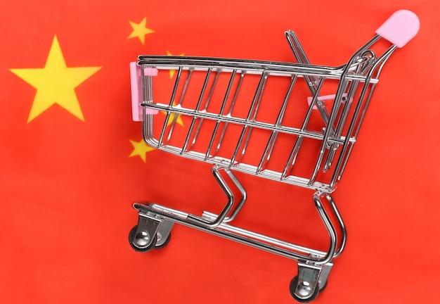 Carrinho de mini supermercado no fundo desfocado da bandeira da china. conceito de compras.