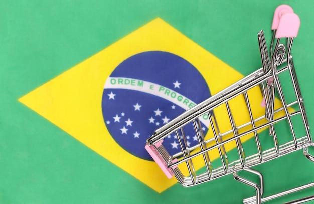 Carrinho de mini supermercado no fundo desfocado da bandeira do brasil. conceito de compras.