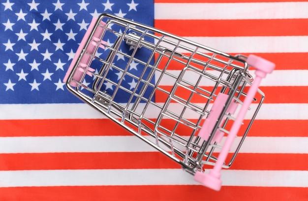 Carrinho de mini supermercado no fundo desfocado da bandeira dos eua. conceito de compras.