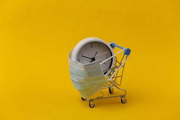 Carrinho de minimercado em máscara médica com relógio em fundo amarelo.