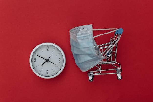 Carrinho de minimercado em máscara médica com relógio sobre fundo vermelho.