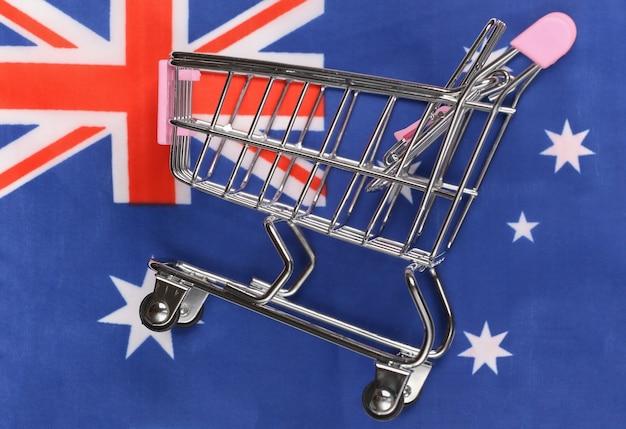 Carrinho de minimercado no fundo desfocado da bandeira da austrália. conceito de compras.