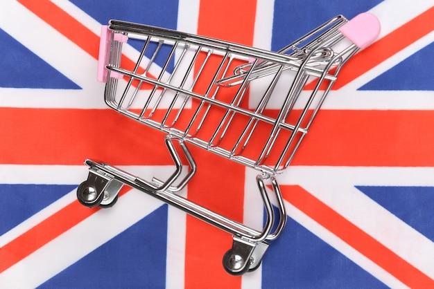 Carrinho de minimercado no fundo desfocado da bandeira da grã-bretanha. conceito de compras.