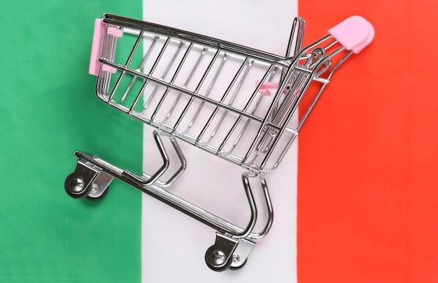 Carrinho de minimercado no fundo desfocado da bandeira da itália. conceito de compras.