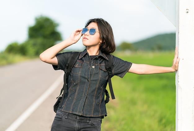 Carrinho de mulher com mochila pedindo carona ao longo de uma estrada