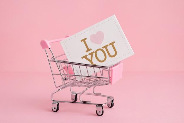 Carrinho de pequeno mercado de compras em um fundo rosa, espaço de cópia, visão lateral do conceito de compras e amor