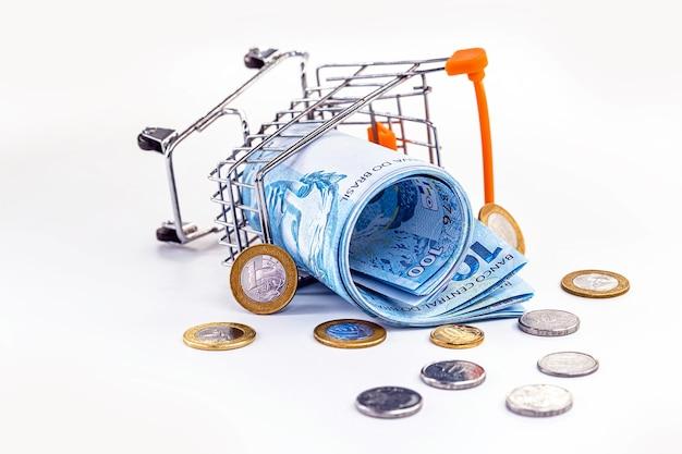 Carrinho de supermercado brasileiro e muito dinheiro espalhado pelo chão. conceito de crise da economia brasileira