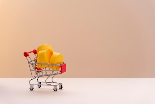 Carrinho de supermercado cheio de plástico amarelo, para reciclar