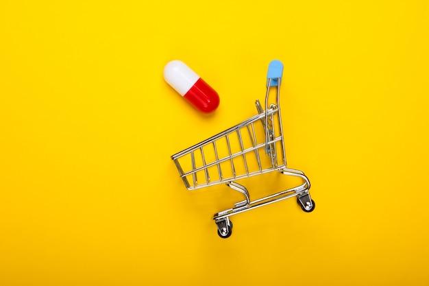 Carrinho de supermercado com cápsula de comprimido em fundo amarelo. vista do topo