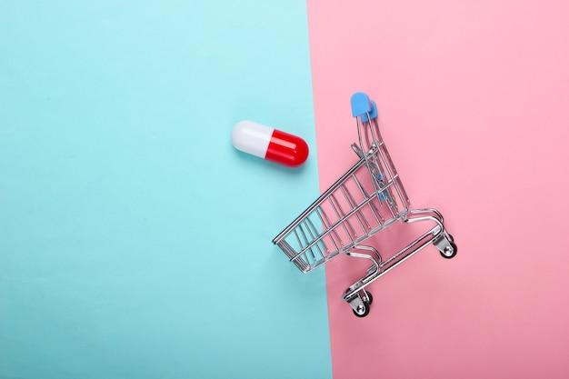 Carrinho de supermercado com cápsula de comprimido em fundo azul-rosa pastel. vista do topo