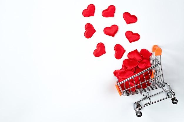 Carrinho de supermercado com corações vermelhos em fundo branco