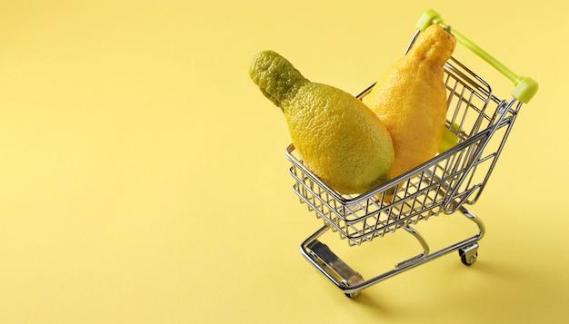 Carrinho de supermercado com dois limões feios na mesa amarela brilhante. conceito de compras ambientais, alimentos orgânicos