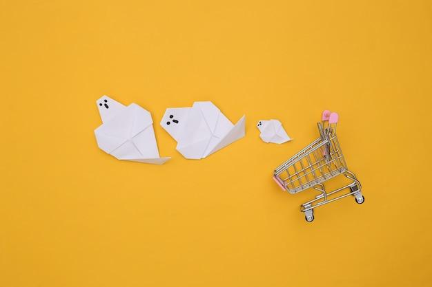 Carrinho de supermercado com fantasmas de origami em fundo amarelo. vista do topo