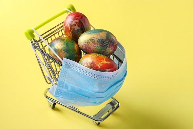 Carrinho de supermercado com máscara protetora com ovos de páscoa em fundo amarelo