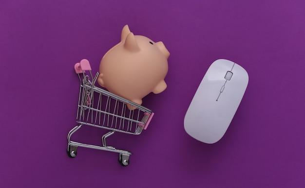 Carrinho de supermercado com mouse de pc, cofrinho em fundo roxo. compras online. vista do topo. postura plana