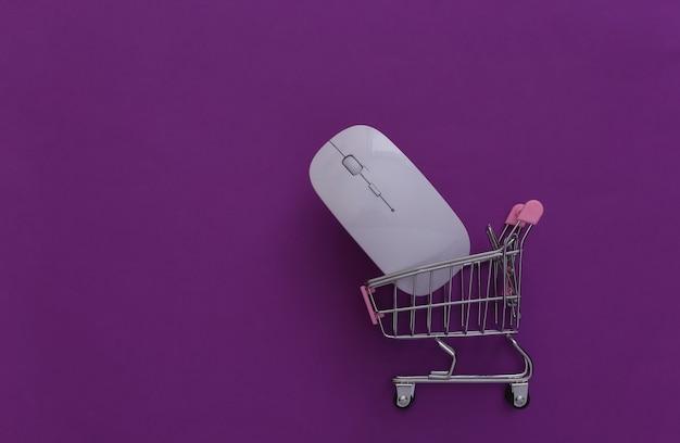 Carrinho de supermercado com o mouse do pc em fundo roxo. compras online. vista do topo